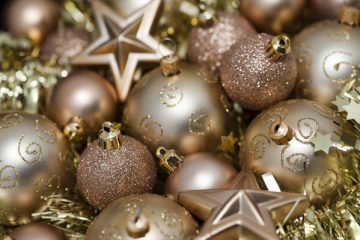 Variety of gold Christmas decorations including baubles, stars, and tinsel for your festive background
